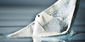 Geld - ein Papierboot aus einem 5-Euro-Schein versinkt