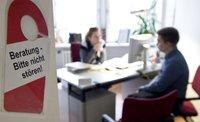 Motiv: Eine Frau sitzt am Scheibtisch, ihr gegenüber ein Mann. An der Tür hängt ein Schild mit dem Text: Beratung bitte nicht stören.