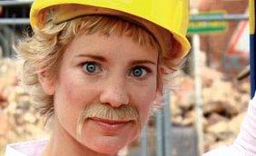 Junge, blonde, blauäugige Frau mit angeklebtem Bart und gelben Bau-Schutzhelm auf einer Baustelle
