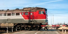 Zug an Bahnübergang mit Schranke